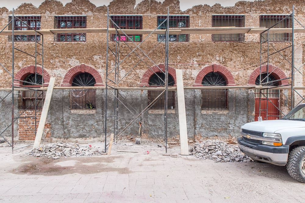 The application of a new layer of plaster and paint to a colonial building front appears to be serious business.