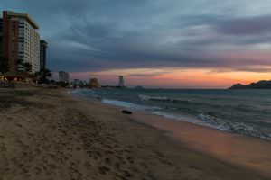 Still a nice sunset, but it loses some of the magic between the high-rise buildings and tyre washed up on shore.